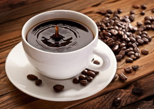Drop falling into a cup of coffee. On a wooden background