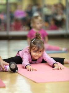 5 year old little girl practices a straddle split during a floor exercise at a gym on the mat (stretching)